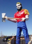 Statue of large bearded man about to bring down his ax over a cable in Tucson, Ariz.